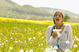 Lady sneezing in a field