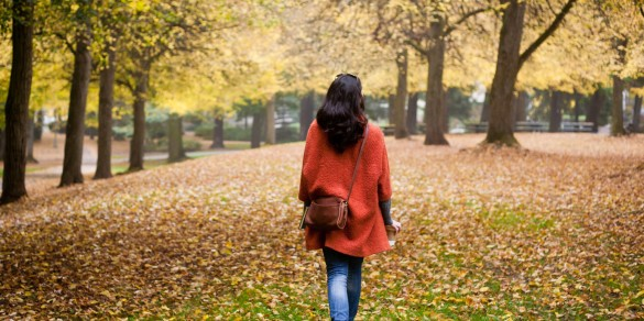 Woman in red coat walking in Autumn leaves